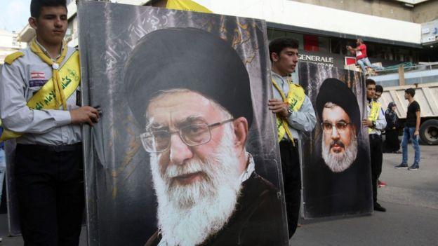 Seguidores de Hezbolá con pancartas que muestran los rostros del ayatolá Alí Jamenei (izquierda), Líder Supremo de Irán, y de Hassan Nasrallah, líder de Hezbolá.