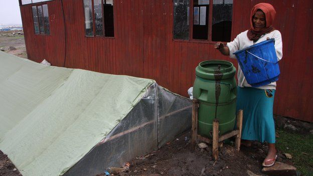 Zenebech Alemayehu mixing cow dung with water to add to her digester