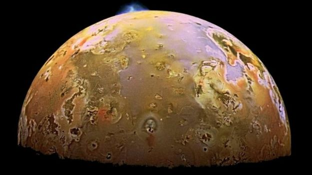 A yellow moon with an erupting volcano