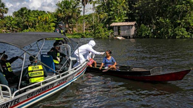 A partir de um barco, profissional todo coberto de jaleco examina mulher em outro barco de madeira, em rio da Amazônia