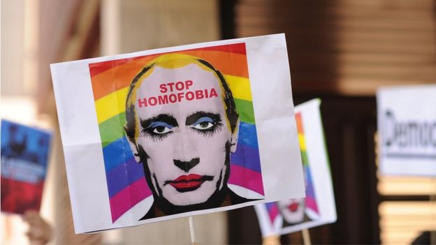 A protestor holds up an image representing Russian President Vladimir Putin wearing lipstick