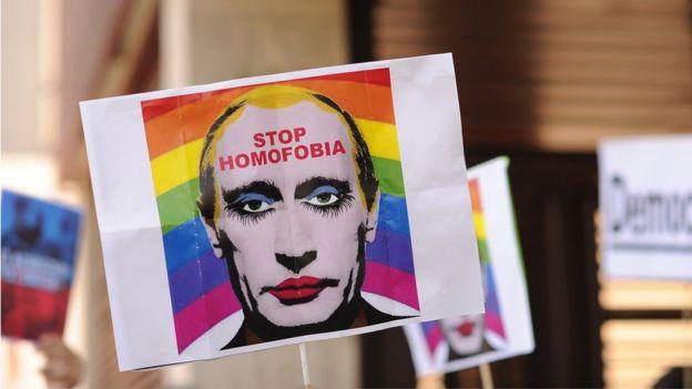 Un manifestante sostiene una imagen que representa a Vladimir Putin con los labios pintados.
