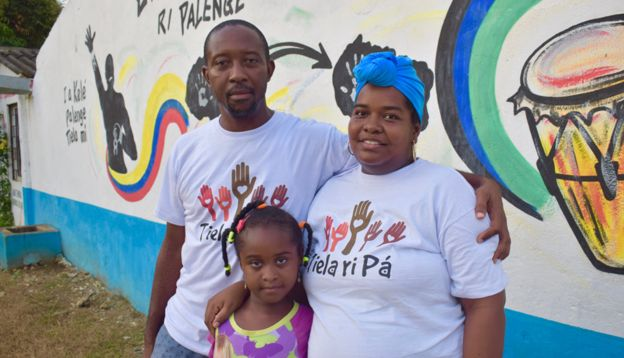 Gustavo Reyes poses in front of a mural with his wife and daughter
