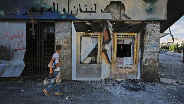 A youth walks with a shoeshine kit past a burnt down branch of a Lebanese bank after it was set on fire and vandalised by protesters earlier, in al-Nour Square in Lebanon's northern port city of Tripoli on 12 June 2020