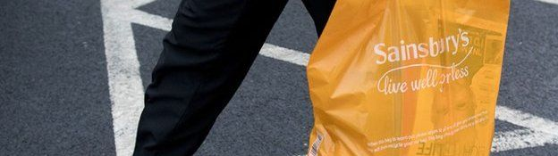 customer walking with an orange Sainsbury's bag