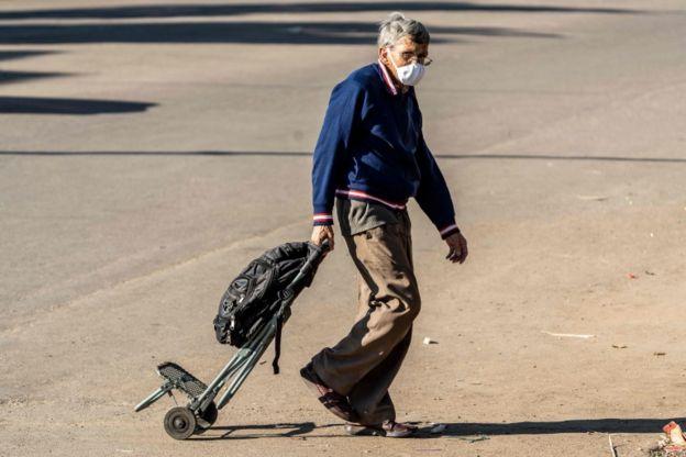 Un hombre mayor con un carro y mascarilla.