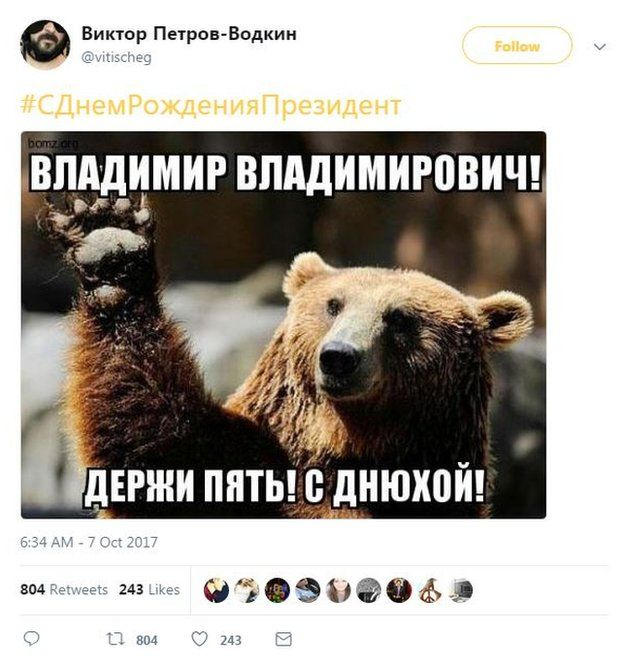 """Picture of a tweet with a photo of a bear extending its paw. The hashtag translates as """"Happy Birthday President"""", and the caption on the photo of the bear says """"Vladimir Vladimirovich (Putin), High five! Happy B-day!"""""""