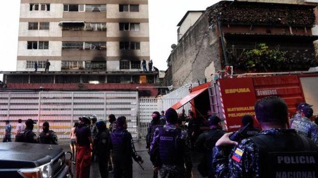 Soldados perto de um prédio com marcas de incêndio