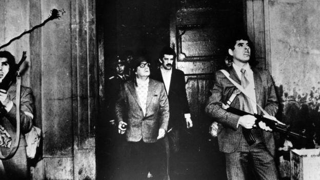 Salvador Allende, con casco y un arma, frente al palacio de la moneda, 11 de septiembre de 1973