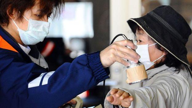 Un hombre mide el nivel de radiación de una mujer cerca de Fukushima, Japón