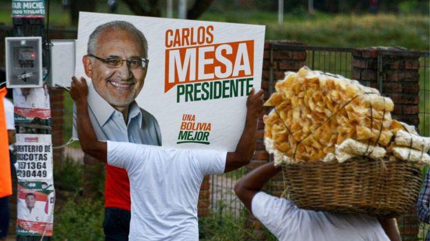 Apoiadores fazem campanha levando cartaz do candidato Carlos Mesa