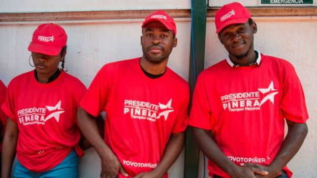 Inmigrantes haitianos con camisetas de apoyo a Piñera en la campaña electoral.