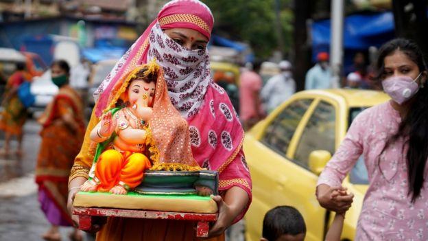 женщина в маске несет статую Ганеша