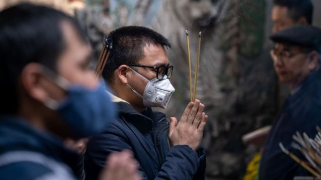 Hai người đàn ông mang khẩu trang thắp nhang cầu nguyện tại một ngôi đền ở Hà Nội hôm 31/1