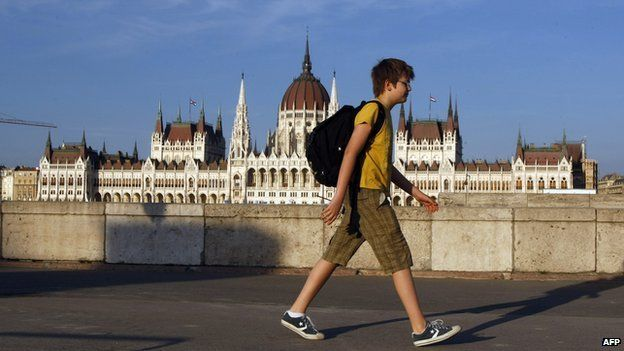 A teenage boy walking in front the Hungarian parliament