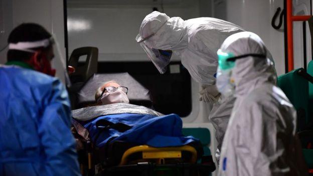 Médicos totalmente cubiertos con un paciente con tapabocas.