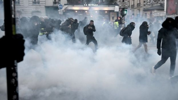 Protesters run away from tear gas during a demonstration in Paris, on January 11, 2020