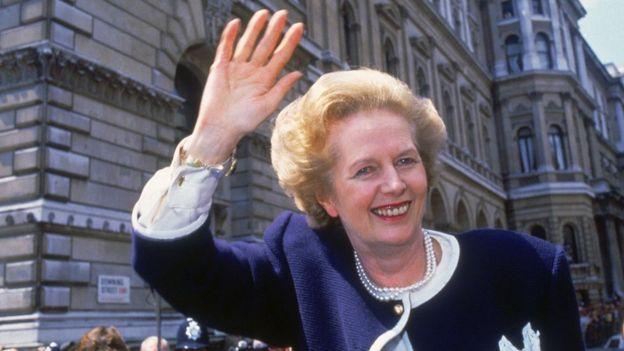 Margaret Thatcher aparece acenando e sorrindo em rua