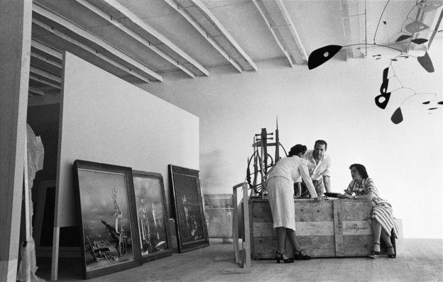 Montagem da I Bienal do Museu de Arte Moderna de São Paulo, esplanada do Trianon, avenida Paulista, 1951. René d'Harnoncourt, diretor do moma, entre duas pessoas não identificadas; à esquerda, pinturas de Yves Tanguy: Divisibilidade indefinida (1942), Os transparentes (1951) e Lentamente para o norte (1951); à direita, móbile Ogunquit (1946), de Alexander Calder
