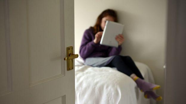 Niña con tableta en el dormitorio