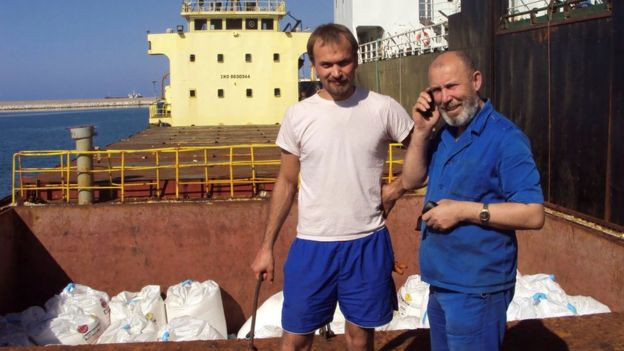 Boris Prokoshev (R), captain of the MV Rhosus, and boatswain Boris Musinchak pose next to a hold loaded with ammonium nitrate in the port of Beirut, Lebanon, in summer 2014