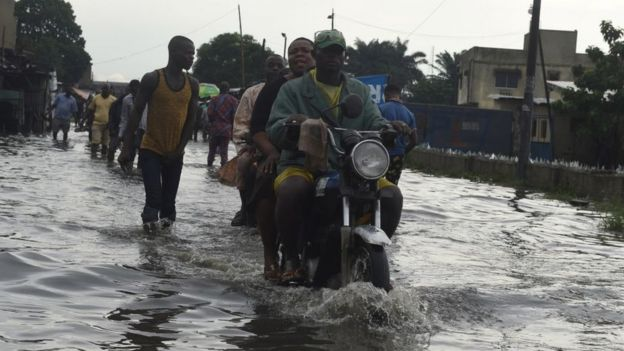 A taxi motocyclist rides on a flooded road at Okokomaiko in Ojo district of Lagos, on May 31, 2017.
