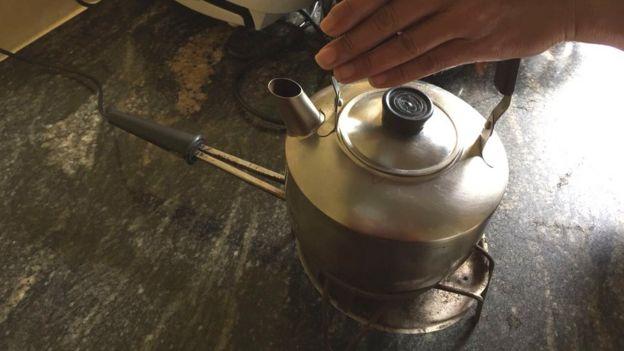 Fogareiro elétrico de uma boca, ligado na tomada, com uma chaleira para ferver água para café