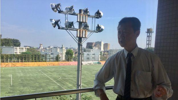 El director de la escuela Kim Seng Fa, detrás el campo de deportes. (Foto: Francisco Jiménez de la Fuente)