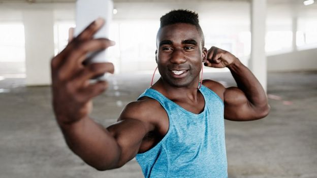 Close-up shot of a sporty young man taking selfies with a mobile phone while working out in an underground parking lot
