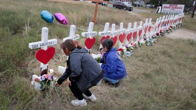 Dos mujeres colocan flores en memoria de víctimas de un tiroteo masivo.