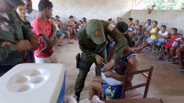 Crianças e famílias observam vacinação realizada com o apoio da Polícia Militar, no Pará