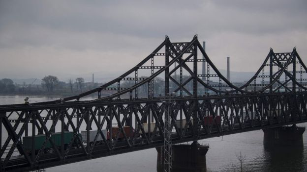 This picture taken on 17 April 2017 shows trucks crossing the Friendship Bridge from the Chinese border city of Dandong to North Korea's Sinuiju over the Yalu river