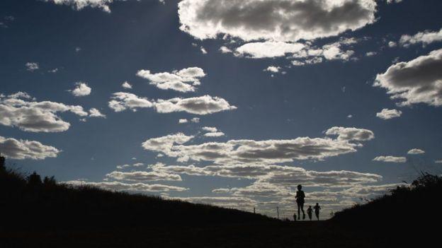 Paisaje con nubes y gente corriendo en Australia.