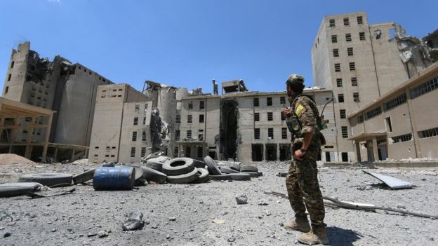 A Syria Democratic Forces (SDF) fighter stands near war-damaged silos and mills of Manbij (1 July 2016)