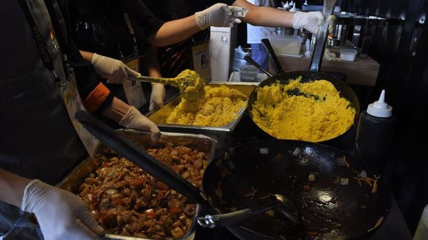 cocineros mueven con un cucharón dos recipientes con comida peruana.