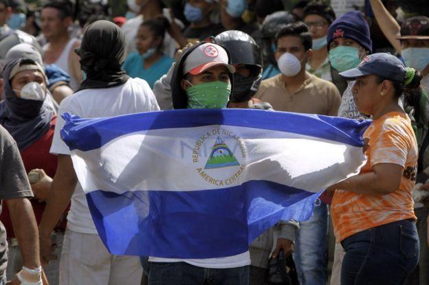 Estudiante con una máscara sosteniendo una bandera de Nicaragua.