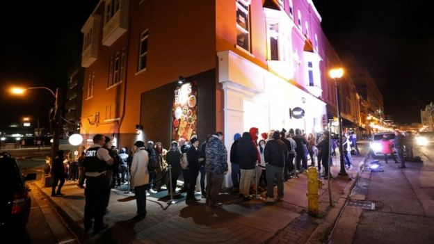 Customers queue outside Tweed, a cannabis shop in St John's Newfoundland, 16 October 2018