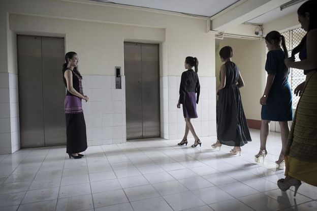 Students practice walking next to Hla Nu Tun, founder of the Style Plus H personal grooming school in Yangon.