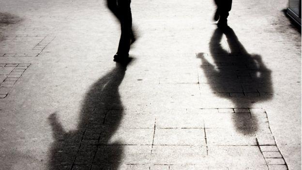 Imagem mostra sombras de duas pessoas no chão