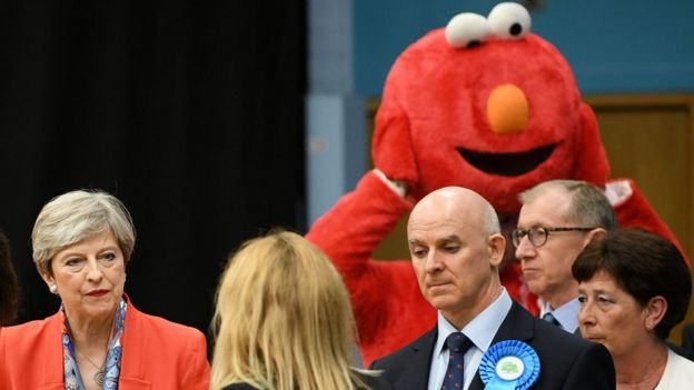 Elmo, Başbakan Theresa May'ın arkasında Maidenhead'deki Mıknatıs Boş Zaman Merkezi'nde, onun yerini tuttuğu tezgâhta bekliyor.