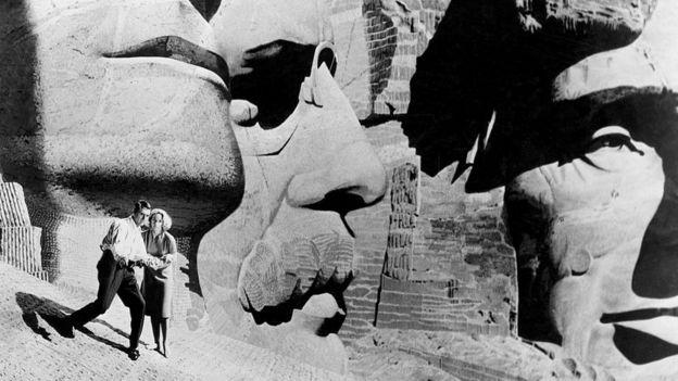 Герои фильма Альфреда Хичкока «К северу через северо-запад» Роджер Торнхилл (Кэри Грант) и Ив Кендал (Эва Мари Сент) прячутся от своих преследователей среди огромных голов президентов на горе Рашмор