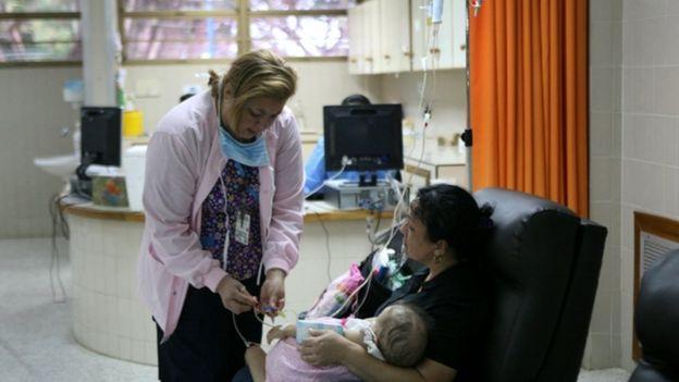 Un bebé en brazos de su madre recibe atención médica