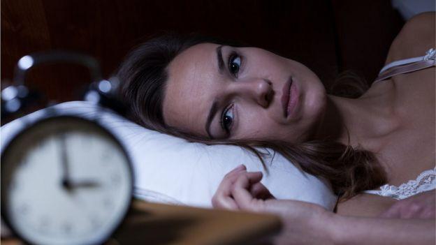 Yatakta saate bakan kadın