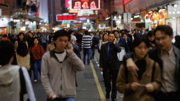 Gente paseando por China usando el celular