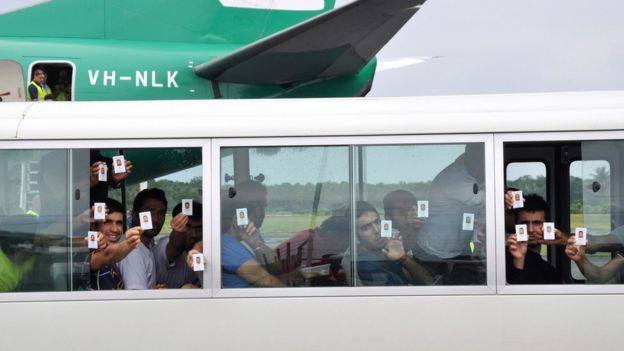 File photo of asylum seekers holding up identity cards after landing in Manus island in Papua New Guinea