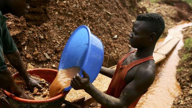 Men sift through dirt and mud while looking for gold 28 March 2006 at an abandoned industrial mine in Mongbwalu, Congo.