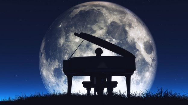 Persona tocando piano con la luna grande detrás.