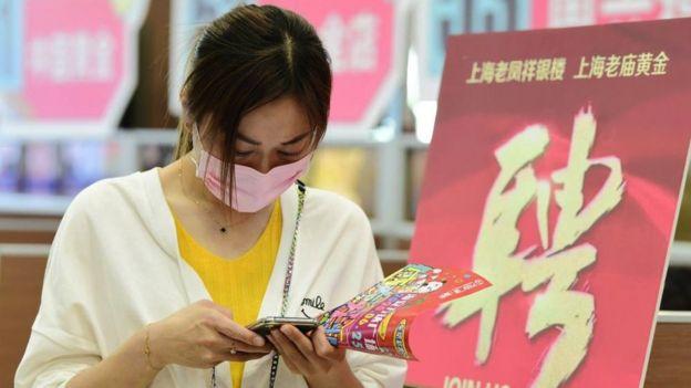 Mulher verifica informações em seu telefone durante uma feira de empregos na cidade de Hai'an, província de Jiangsu, China, em maio de 2020