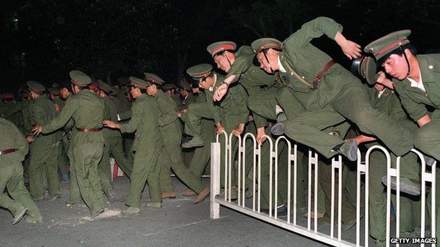 People Liberation Army (PLA) soldiers leap over a barrier on Tiananmen Square in central Beijing 4 June 1989 during heavy clashes with people and dissident students. On the night of 3 and 4 June 1989, Tiananmen Square sheltered the last pro-democracy supporters