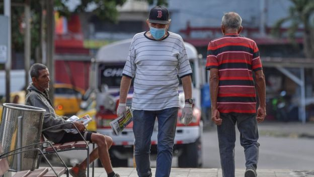 A man wearing a face mask as a precautionary measure against the spread of the new coronavirus walks in Panama City